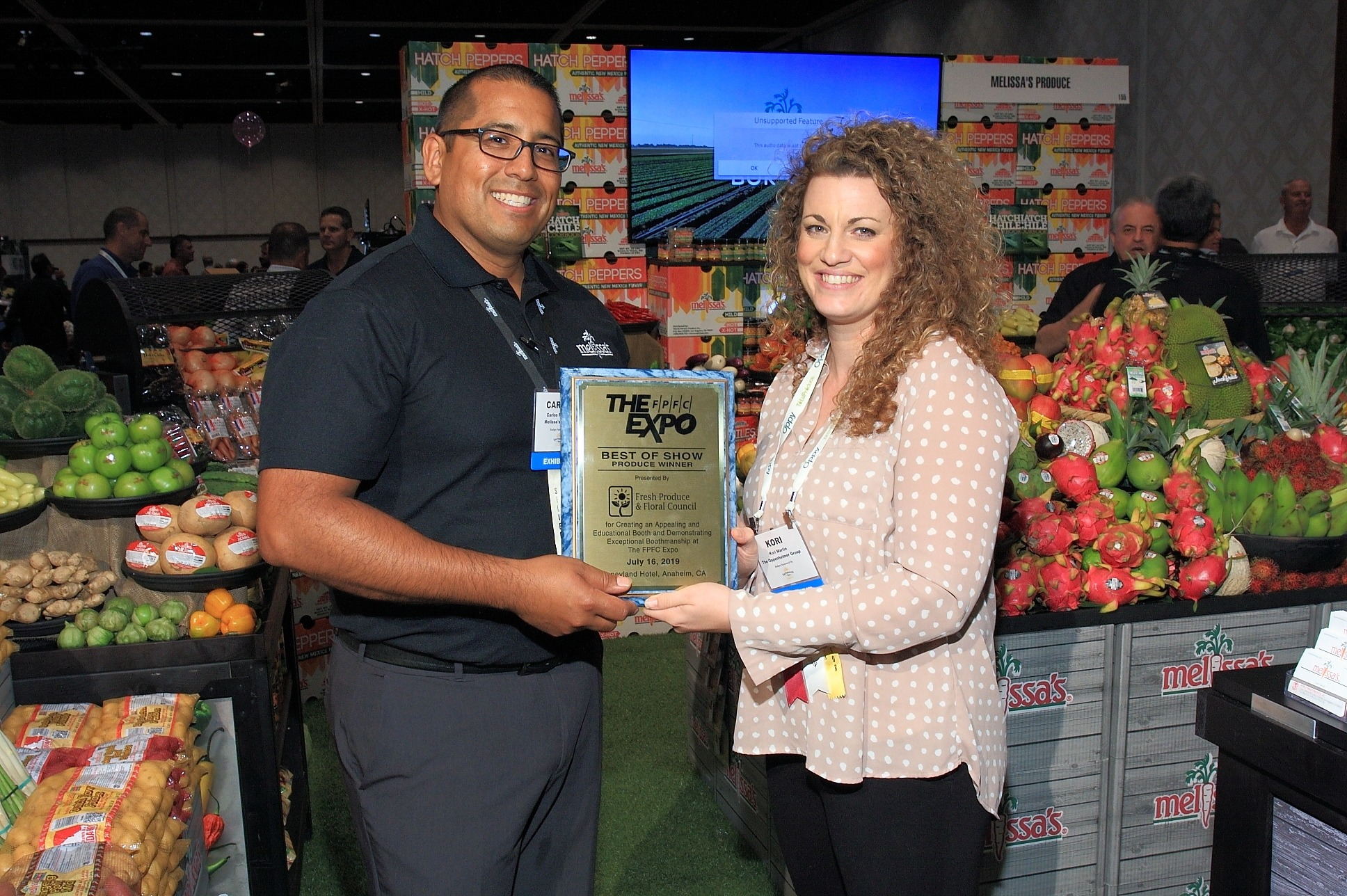 Carlos Preciado from Melissa's Produce accepts the Produce Best of Show Award from Expo Committee Chair Kori Martin from The Oppenheimer Group
