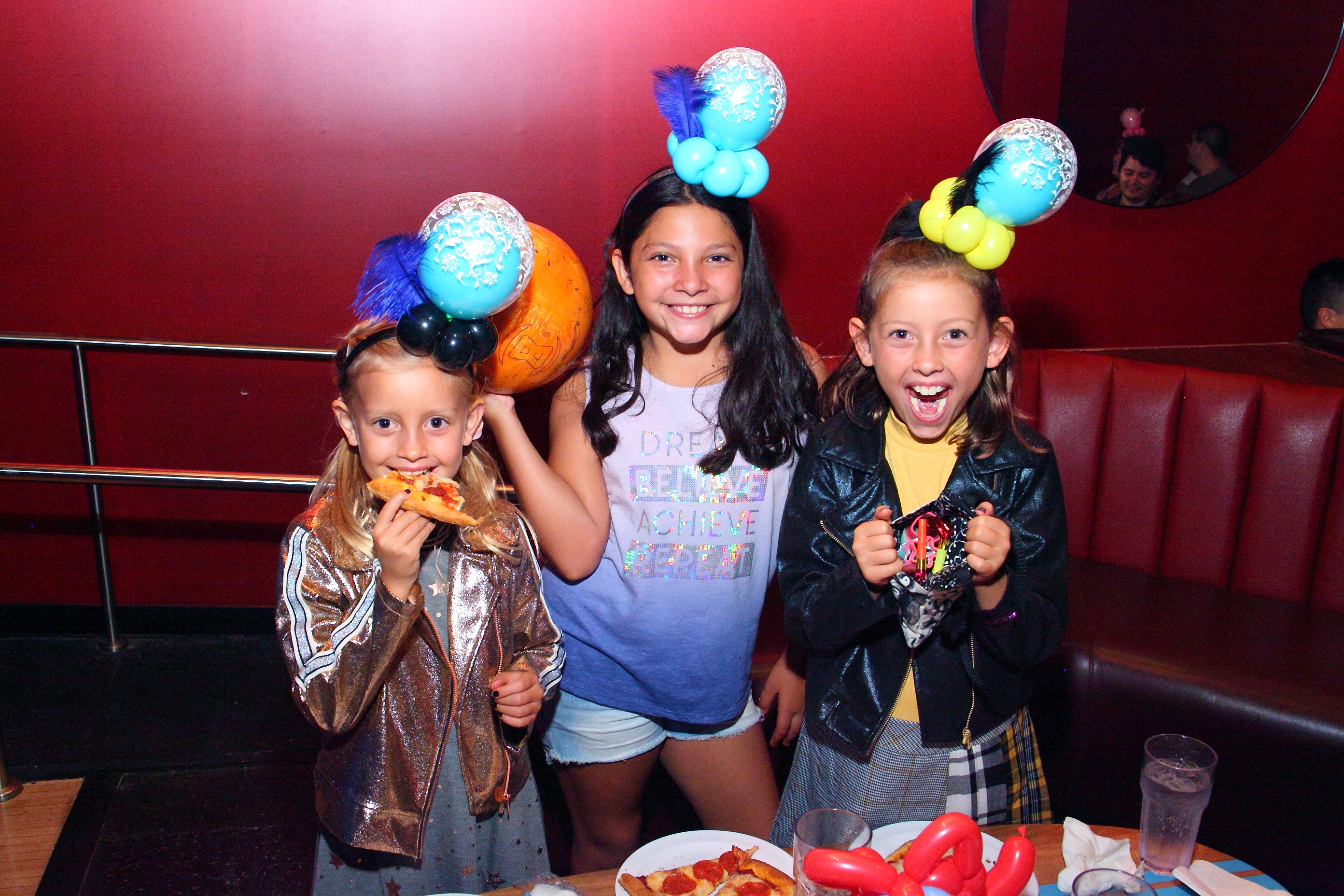 The kids staying entertained with balloon hats and pizza!